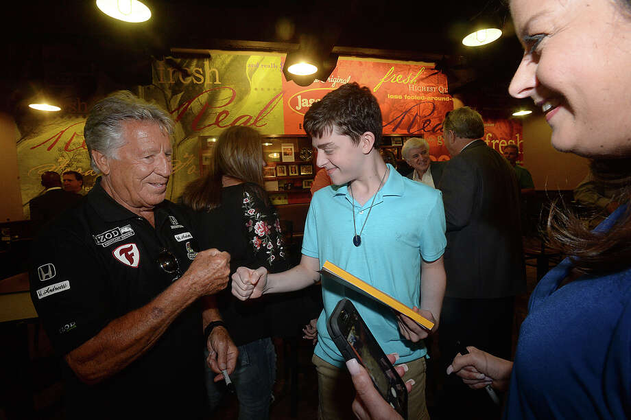 Famous race car driver Mario Andretti gives a fist bump to  fan Nate Graham as his mother Amy looks on as he makes his way in during a meet and greet rally at Jason's Deli in the Gateway Plaza Thursday. The event was the first social stop for Andretti, who was the celebrity host at this year's Champagne and Ribs fundraising gala Thursday night.  Photo taken Thursday, April 20, 2017 Kim Brent/The Enterprise Photo: Kim Brent / BEN