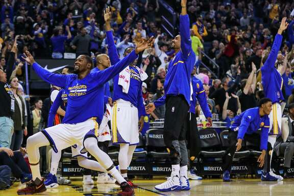 Golden State Warriors' basketball team reacts after Klay Thompson scored a 3-pointer in a game against the Indiana Pacers, in Oakland, California, on Monday, Dec. 5, 2016.