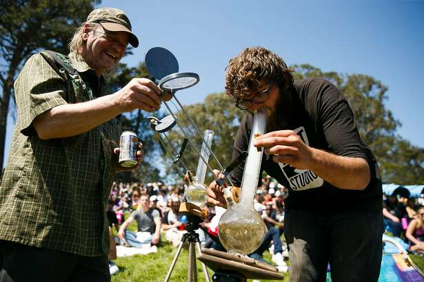 Trevor Hanson takes a hit off a high beam solar bong as Tom Wilhelm, left, offers a helping hand during the annual 4/20 celebration near Hippie Hill at Golden Gate Park in San Francisco, Calif. Thursday, April 20, 2017.