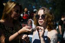 Kara Dorton, left, assists Rheanna Patton with the joint during the annual 4/20 celebration on Hippie Hill at Golden Gate Park in San Francisco, Calif. Thursday, April 20, 2017.