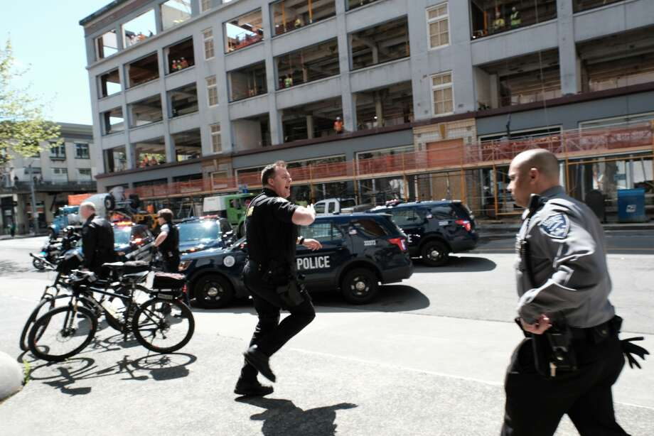 Seattle police pursue suspects at the scene where two cops were shot during a robbery response downtown Thursday afternoon. Photo: Dean Wenick/special To Seattlepi.com