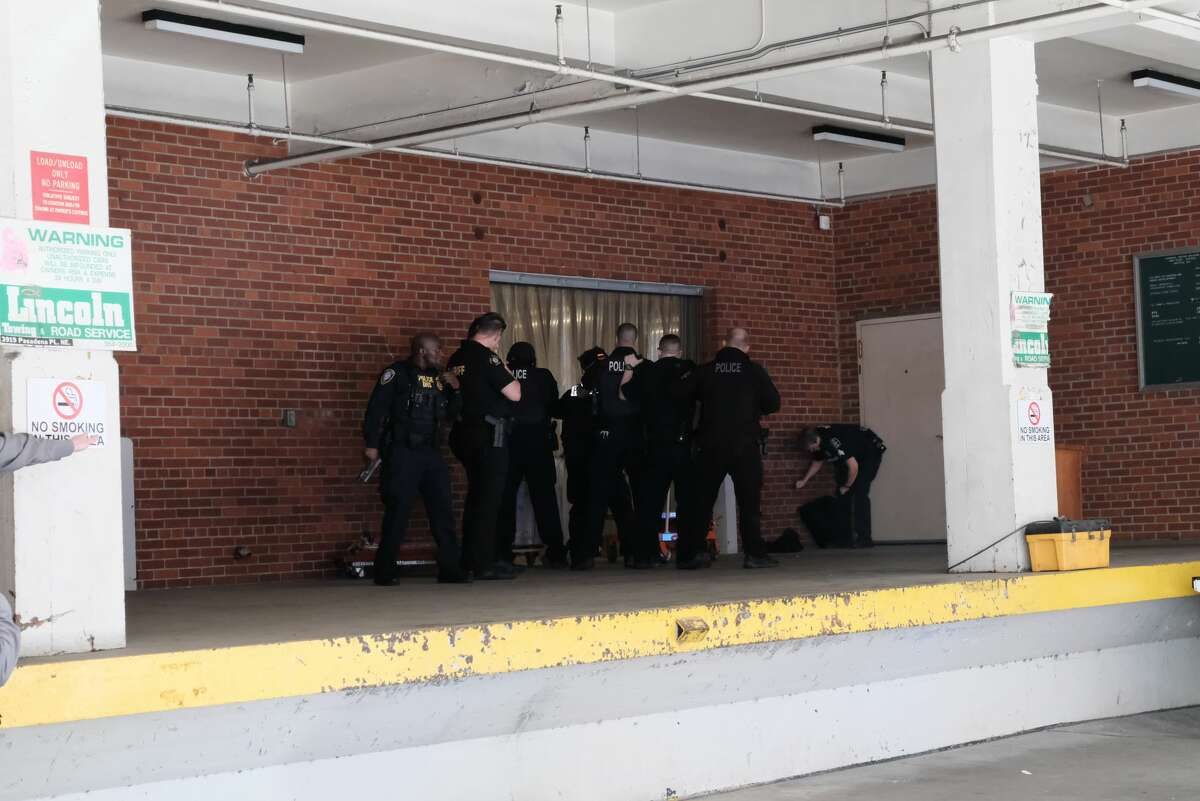 Seattle police pursue suspects at the scene where two cops were shot during a robbery response downtown Thursday afternoon.
