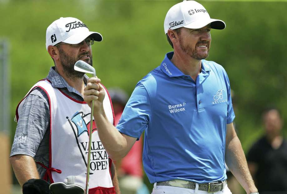 Jimmy Walker pulls an iron from his bag to hit to the par three third hole during the first round of the Valero Texas Open at TPC San Antonio Oaks Course on April 20, 2017. Caddy Andy Sanders looks over the bag. Photo: Tom Reel, Staff / San Antonio Express-News / 2017 SAN ANTONIO EXPRESS-NEWS