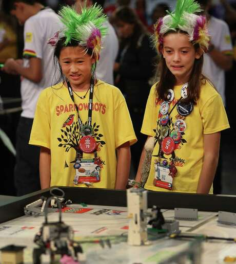Loan Hoang (left) and Iris Ochoa of Team Sparrowbots react to their robot's performance Thursday at the George R. Brown Convention Center. More than 15,000 students  from 24 states and 33 countries are competing.  Photo: Steve Gonzales, Staff / © 2017 Houston Chronicle