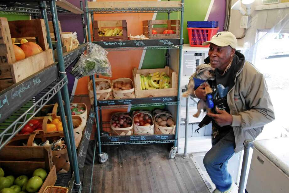 "Horace Peterson, comes into the Capital Roots Veggie Mobile outside of Kennedy Towers to buy some produce on Thursday, April 20, 2017, in Troy, N.Y.  Ten years ago the Capital Roots Veggie Mobile began bringing fresh produce to Troy, Albany and Schenectady, with the Kennedy Towers being its first ever stop.  When it started the Veggie Mobile had stops in the three cities three days a week, today they visit 6 area cities and towns, five days a week, making 35 stops.  Amy Klein, the CEO of Capital Roots, said that some people doubted that it would work but on the very first stop at Kennedy Towers ""people were lined up and we knew we had a success on our hand"" she said.  ""We bring them top quality veggies, not seconds, and were supporting 65 local farms year round"" Klein added.  (Paul Buckowski / Times Union) Photo: PAUL BUCKOWSKI / 20040321A"
