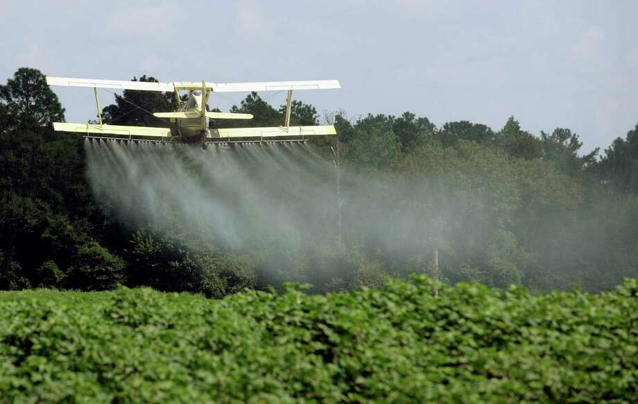 In this photo taken Aug. 4, 2009 file photo, a crop duster sprays a field of crops just outside Headland, Ala. Dow Chemical is pushing the Trump administration to scrap the findings of federal scientists who point to a family of widely used pesticides as harmful to about 1,800 critically threatened or endangered species. (AP Photo/Dave Martin, File) Photo: Dave Martin, STF / AP2009