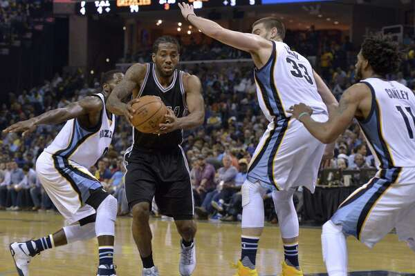 San Antonio Spurs forward Kawhi Leonard (2) drives between Memphis Grizzlies forward JaMychal Green, left, center Marc Gasol (33), and guard Mike Conley (11) during the second half of Game 3 in an NBA basketball first-round playoff series Thursday, April 20, 2017, in Memphis, Tenn. (AP Photo/Brandon Dill)