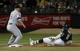 Oakland Athletics' Rajai Davis (11) slides safely into third next to Seattle Mariners third baseman Kyle Seager after a single by Davis followed by an error by Mariners center fielder Leonys Martin during the fifth inning of a baseball game Thursday, April 20, 2017, in Oakland, Calif. (AP Photo/Marcio Jose Sanchez)