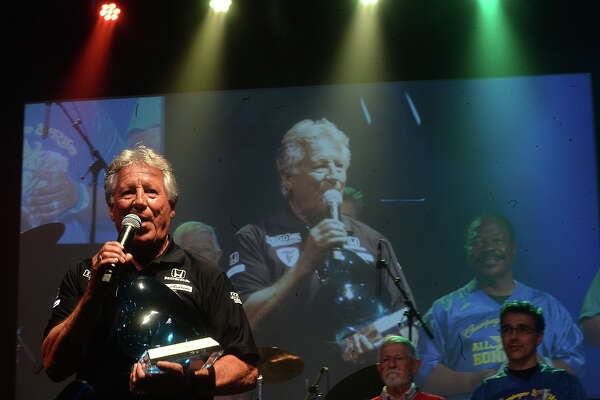 """Mario Andretti addresses the crowd at this year's Champagne & Ribs fundraising gala at Ford Park Thursday. The theme of this year's event was """"Southeast Texas Wide World of Sports,"""" and featured local All-Star honorees """"Big"""" Rich Courville, Judge Donald Floyd, Fernando Salazar, and Dr. George Thomas. Bag of Donuts entertained as attendees spent the night dining, drinking, dancing, bidding at the silent auction, and enjoying the appearance by famous race car driver Mario Andretti.  Proceeds from the popular annual event benefit the Gift of Life's Men's Health and Prostate Cancer Program, which provides services for local men in need. Photo taken Thursday, April 20, 2017 Kim Brent/The Enterprise"""