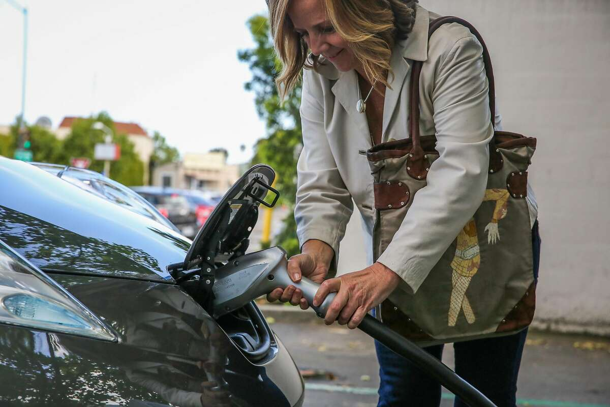 Carleen Cullen unplugs her electric car after demonstrating how to charge it in the parking lot of United market in San Rafael, California, on Thursday, April 20, 2017.