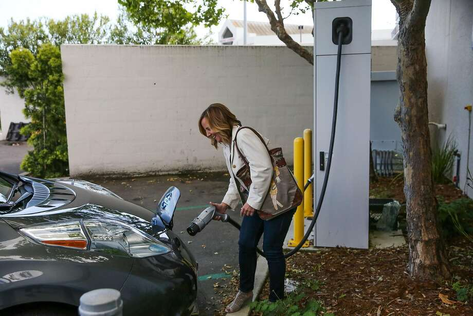 Carleen Cullen unplugs her electric car after demonstrating how to charge it in the parking lot of a  market in San Rafael, on Thursday. Cullen wants more chargers along I-5, to make it easier to traverse the state in an electric vehicle. Photo: Gabrielle Lurie, The Chronicle
