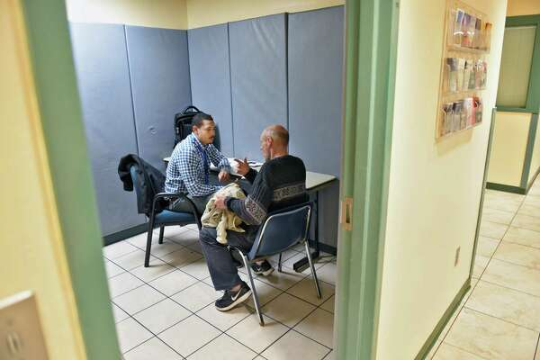 Whitney Young Health outreach specialist Hezekiah Morris, left, goes over medical information during a program at the Capital City Rescue Mission Tuesday April 18, 2017 in Albany, NY.  (John Carl D'Annibale / Times Union)
