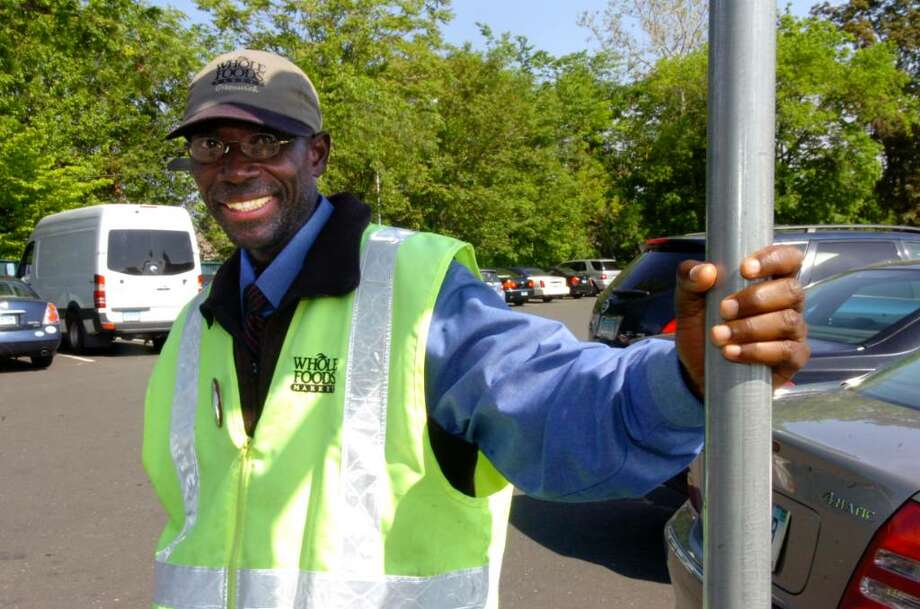 Patrick Lamothe takes a break from directing traffic recently at Whole Foods Market on East Putnam Avenue in Greenwich. Photo: Helen Neafsey / Greenwich Time