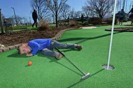 Eason Brooks, 4, of Darien eyes up his putt as he and his family play miniature golf at Cove Marina April 14 in Norwalk.