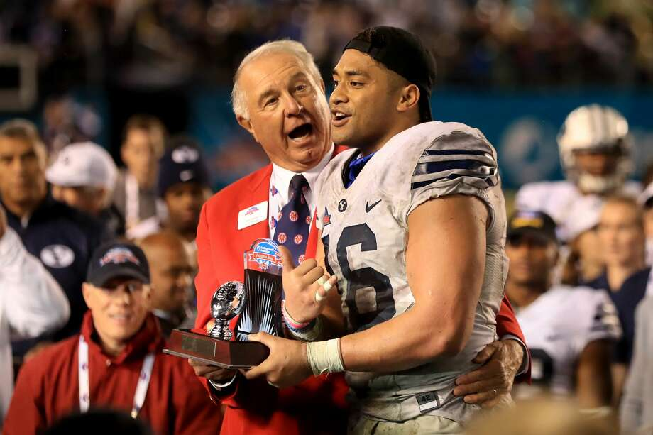SAN DIEGO, CA - DECEMBER 21:  President of the San Diego County Credit Union Poinsettia Bowl Ted Tollner congratulates Harvey Langi #16 of the Brigham Young Cougars  for winning the Defensive Player of the game after defeating the Wyoming Cowboys 24-21 in a game on December 21, 2016 in San Diego, California.  (Photo by Sean M. Haffey/Getty Images) Photo: Sean M. Haffey/Getty Images