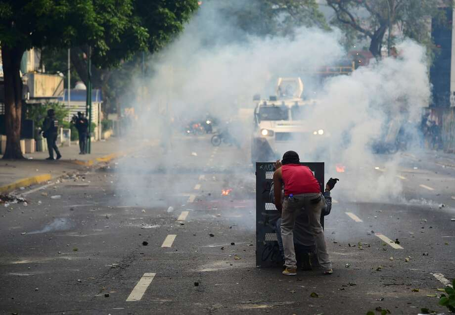 A demonstrator clashes with the police during a rally against Venezuelan President Nicolas Maduro, in Caracas on April 19, 2017. Venezuelans took to the streets Wednesday for massive demonstrations for and against President Nicolas Maduro, whose push to tighten his grip on power has triggered deadly unrest that has escalated the country's political and economic crisis. / AFP PHOTO / RONALDO SCHEMIDT        (Photo credit should read RONALDO SCHEMIDT/AFP/Getty Images) Photo: RONALDO SCHEMIDT/AFP/Getty Images