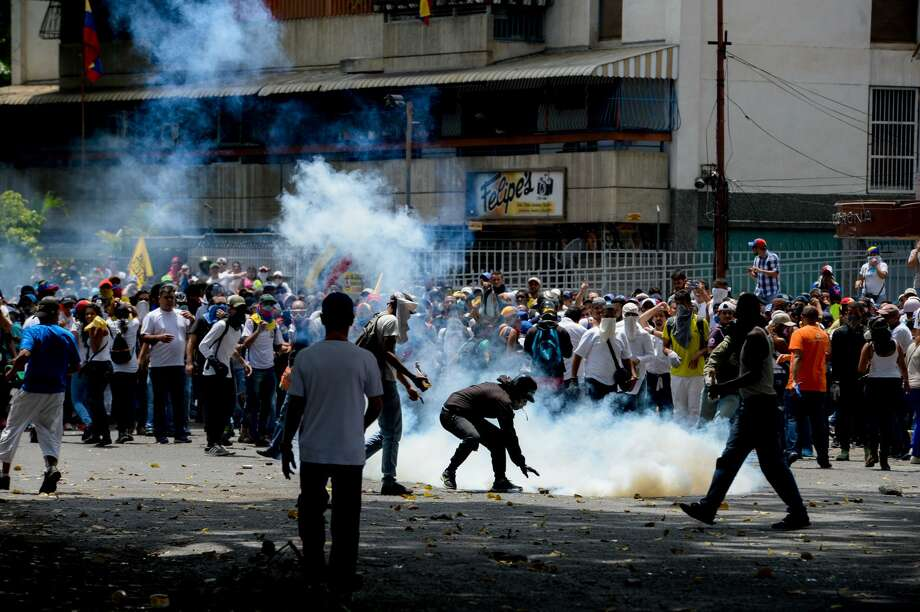 Demonstrators clash with riot police during a march against Venezuelan President Nicolas Maduro, in Caracas on April 19, 2017. Venezuelans took to the streets Wednesday for massive demonstrations for and against President Nicolas Maduro, whose push to tighten his grip on power has triggered deadly unrest that has escalated the country's political and economic crisis. / AFP PHOTO / FEDERICO PARRA        (Photo credit should read FEDERICO PARRA/AFP/Getty Images) Photo: FEDERICO PARRA/AFP/Getty Images