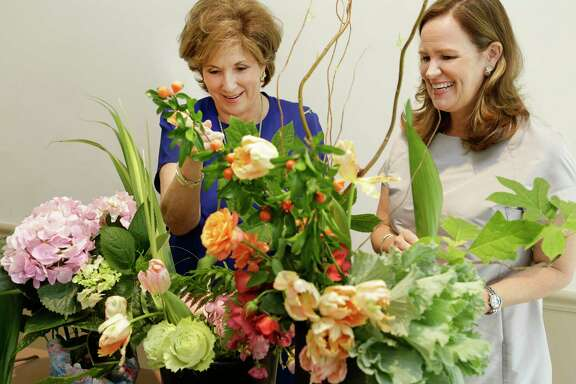 Carole Bailey, left, and Sara Ledbetter demonstrate some of the floral-design techniques that will be on display during the Florescence competition.