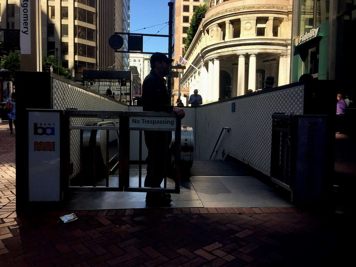A service employee guards the entrance of the out of service Montgomery Bart station During a widespread power outage in San Francisco on Friday, April 21, 2017.