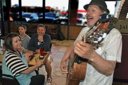 Mr. and Mrs. Ryan Rhodes and son Michael listen to Manuel Jimenez Villalobos perform while dining at Taqueria Jalisco on Tuesday night.