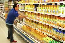 ShopRite employee Greg Gaudiosi straightens out the orange juice section at the store's Danbury, Conn., store on Friday, April 21, 2017. The store's refrigeration system utilizes new technology that makes cooling food more energy efficient.