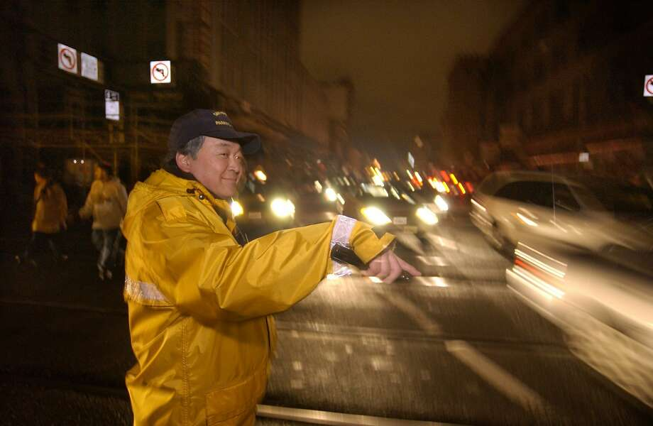 A traffic control officer directs traffic during a blackout in San Francisco on Dec. 20, 2003, when a fire at a PG&E substation knocked out electricity to 120,000 customers. Despite Friday's blackout, which affected 95,000 customers, PG&E's record on power outages is improving. Photo: KIM KOMENICH, AP