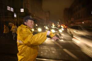 Bryan Tanabe, traffic control officer directs blackout traffic at Taylor and Market Streets in San Francisco, Saturday, Dec. 20, 2003. A fire at an electrical substation has caused a widespread power outage here affecting about 120,000 customers, the Pacific Gas & Electric Company said. (AP Photo/The Chronicle, Kim Komenich)