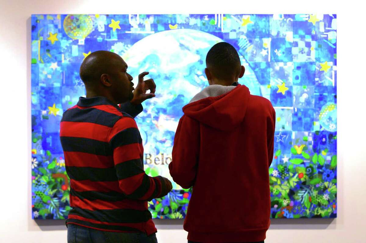 Leon Smith, of Bridgeport, and his son Kahlil, 14, check out artwork during the opening night of the