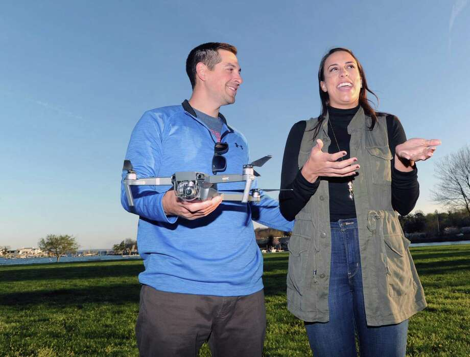 Michael Stempien holds his drone as his fiancee Michelle Garone speaks at Roger Sherman Baldwin Park in Greenwich, Conn., Tuesday evening, April 18, 2017. Stempien, a Greenwich native, used his drone, made by Autel, to film his proposal to Garone this past September. In January his video was selected as a finalist in the drone maker Autel Robotics' X-Star video contest. Photo: Bob Luckey Jr. / Hearst Connecticut Media / Greenwich Time