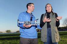 Michael Stempien holds his drone as his fiancee Michelle Garone speaks at Roger Sherman Baldwin Park in Greenwich, Conn., Tuesday evening, April 18, 2017. Stempien, a Greenwich native, used his drone, made by Autel, to film his proposal to Garone this past September. In January his video was selected as a finalist in the drone maker Autel Robotics' X-Star video contest.