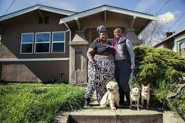 Merika Reagan, left (pink hair), and Ifasina Clear of Oakland are fighting for rent control protections for their home. State law exempts single family homes such as their home from local rent control laws such as Oakland. The landlord is an investment company that owns 23,000 homes nationwide.