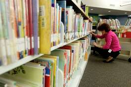Natalia Martakova reshelves books at the George and Cynthia Woods Mitchell Library, Wednesday, April 20, 2017, in The Woodlands. The library is a finalist for the 2017 National Medal for Museum and Library Service by the Institute for Museum and Library Services. The award is the nationé•s highest honor given to museums and libraries for service to the community. The branch is one of only 15 libraries selected as finalists for the award this year, and is the only Texas institution to be honored in 2017.