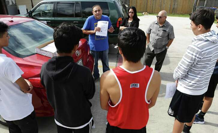 Jason Mata, center, a leader of the Prospect Hill Neighbhorhood Association and head of a youth boxing program, instructs volunteers April 14, 2017, on how to gather signatures for a petition requesting a police storefront on North Zarzamora Street in Prospect Hill.