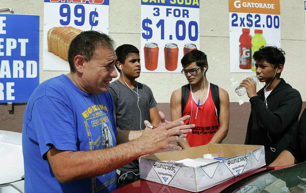 Jason Mata, left, executive director of The Advocates Boxing Youth Program, instructs volunteers, from left to right, Chris Churbe, Sebastian Sanchez and Merced Garcia on how to gather signatures for a petition requesting a police storefront in Prospect Hill. Last year, there were four homicides in the neighborhood. Residents also say they've seen an increase in armed robberies and prostitution.