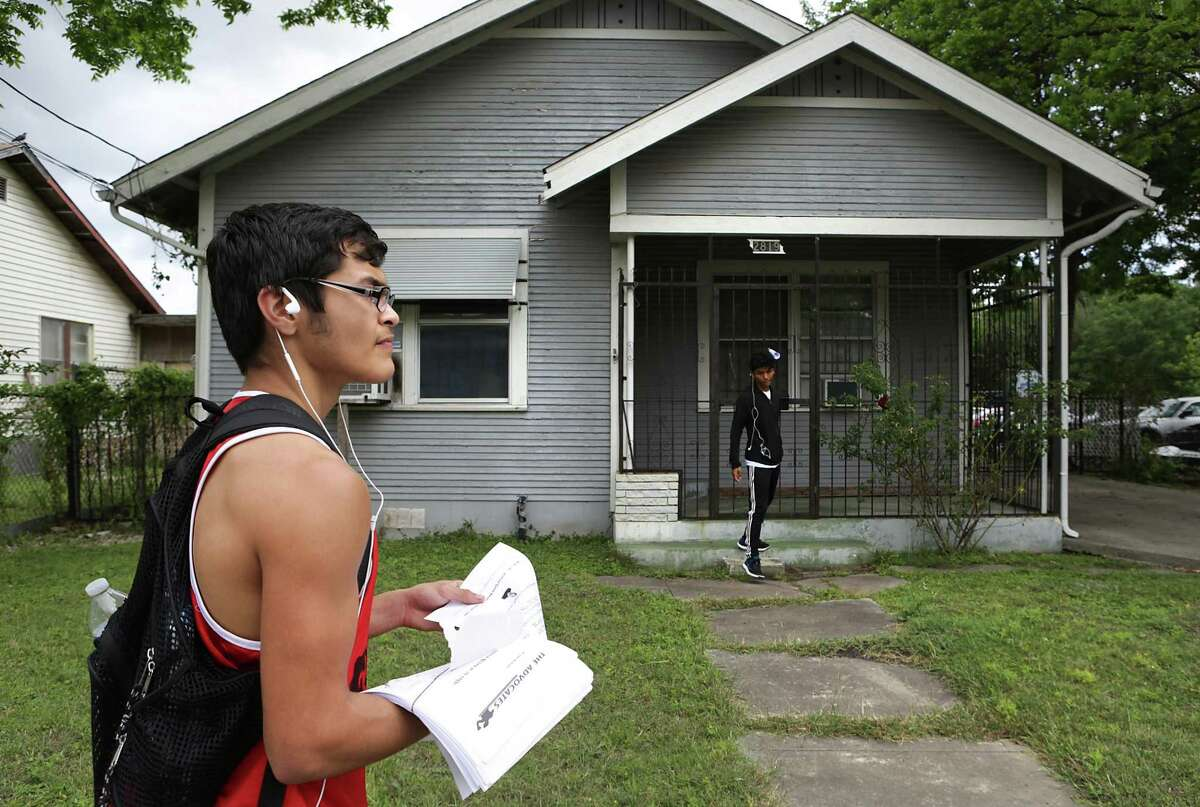 Sebastian Sanchez, left, looks down Martin Street as Merced Garcia places a flyer at a house on April 14, 2017. In response to an increase of crime, a group of Prospect Hill residents is circulating a petition to add a police storefront in the neighborhood. So far, the residents have collected roughly 350 signatures.