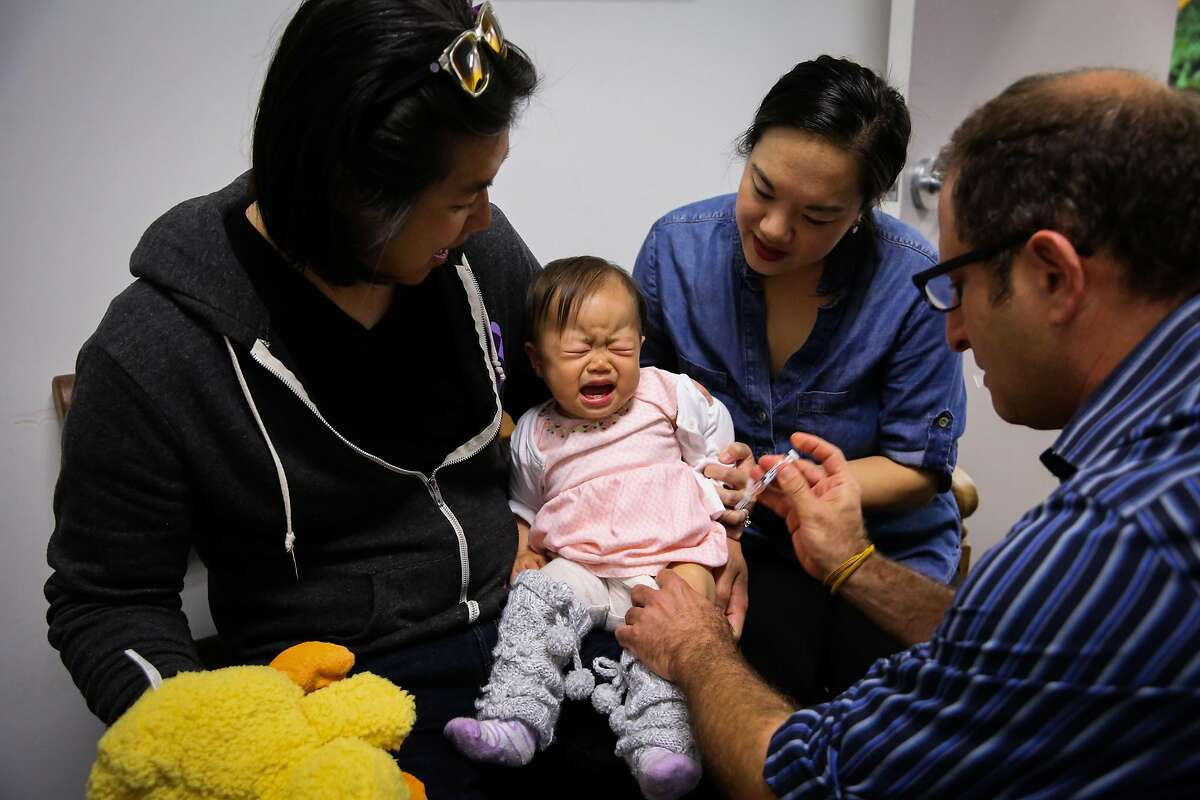 Dr. Oded Herbsman (right) vaccinates baby Hazel Hua, 12 months, while parents David Hua (left) and Stephanie Hua (second from right) hold her close, in San Francisco, California, on Monday, April 17, 2017.