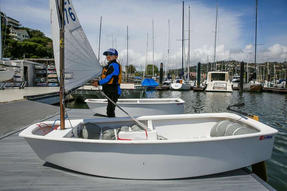 Rhett Krawitt, 9 (right) sets up his sailboat before sailing practice in Tiburon, California, on Wednesday, April 19, 2017. Rhett cannot be vaccinated because he is immune compromised due to having leukemia as a child. Photo: Gabrielle Lurie, The Chronicle
