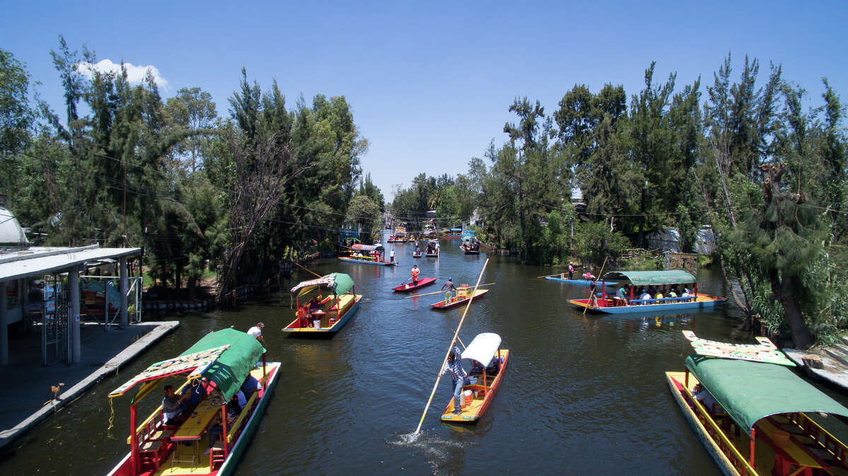 Aerial view taken with a drone of 'trajineras' -traditional flat-bottomed river boat- at Xochimilco natural reserve in Mexico City on April 1, 2016. Xochimilco canals are one of the places most visited by local and foreign tourists, to go along the water, eat traditional food and enjoy Mariachi music.
