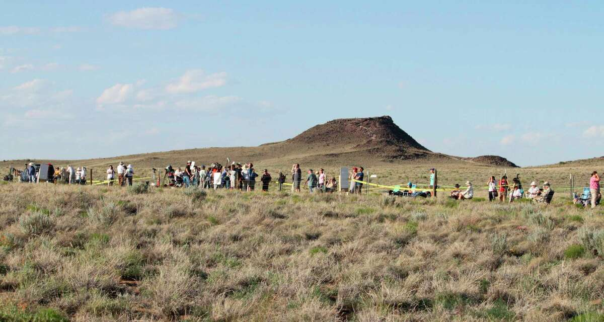 FILE - In this May 20, 2012 file photo, people line the fence line at the Petroglyph National Monument near Albuquerque, N.M., to watch the annular solar eclipse.