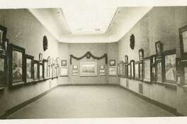The vintage photograph was taken at one of the first exhibitions of the Greenwich Art Society, around 1918, at the Bruce Museum.