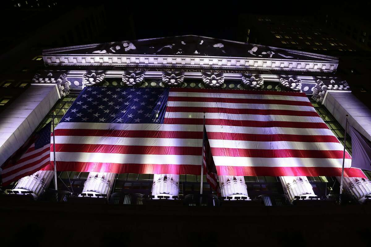 In this evening Friday, Feb. 17, 2017, photo, an American flag hangs on the front of the New York Stock Exchange. European stocks declined while most Asian markets rose Friday, April 21, 2017, ahead of the first round of voting in France's closely watched presidential election. (AP Photo/Peter Morgan)