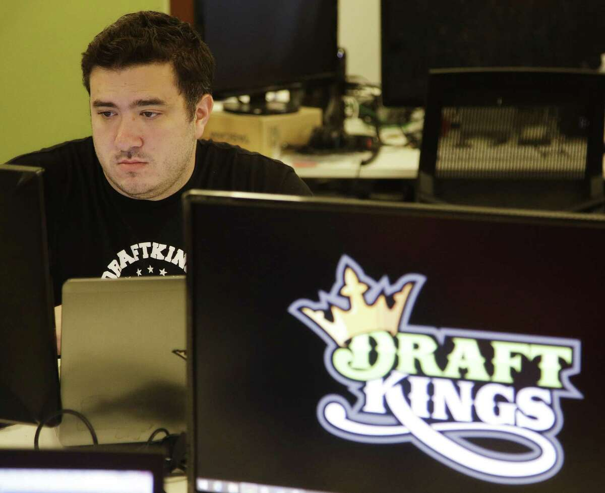 A DraftKings employee works at his station at the daily fantasy sports company's offices in Boston. The daily fantasy sports industry has contracted starkly since questions about the legality of online games offered by companies sparked court and legislative battles across the U.S. last year.