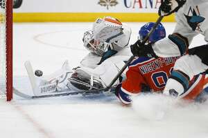 San Jose Sharks goalie Martin Jones, left, dives for the puck as Edmonton Oilers' Ryan Nugent-Hopkins crashes into him during overtime of Game 5 of a first-round NHL hockey Stanley Cup playoff series, Thursday, April 20, 2017, in Edmonton, Alberta. The Oilers won 4-3. (Jeff McIntosh/The Canadian Press via AP)