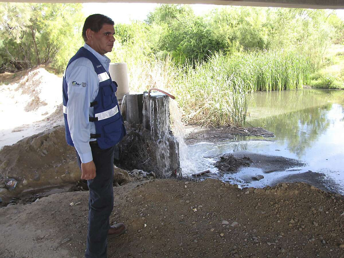 Javier Saavedra, who heads a section of the Nuevo Laredo water utility COMAPA, inspects sewage water gushing into a creek that reaches the Rio Grande. Utilities along both sides of the border have relied since NAFTA on joint U.S.-Mexico loans and grants, monies threatened by proposed cancellation of EPA border programs and uncertainty about future U.S.-Mexico relations.