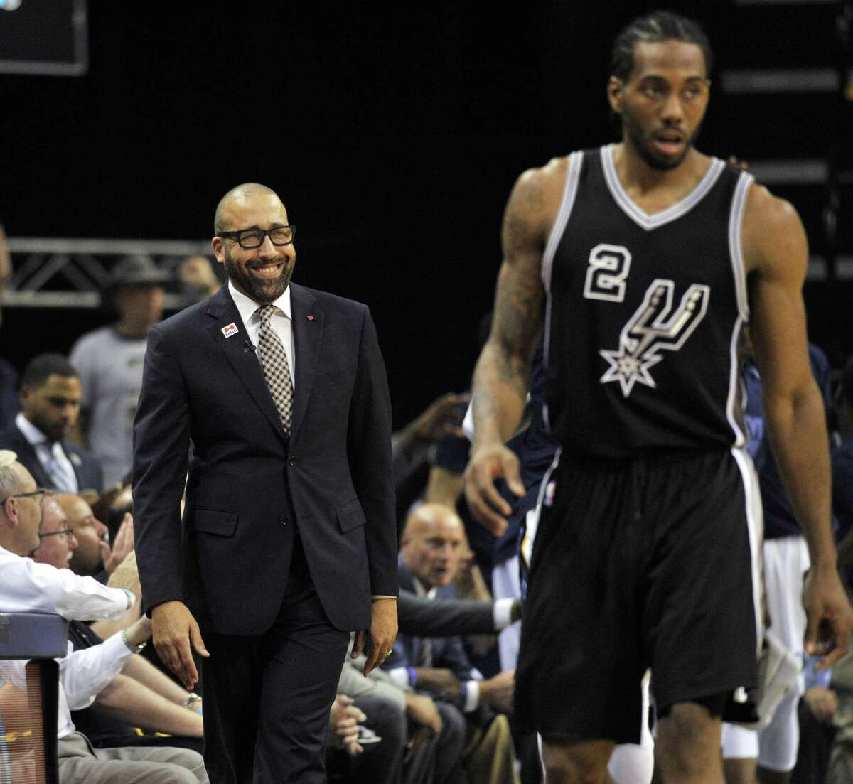 Grizzlies coach David Fizdale smiles from the sideline as Spurs forward Kawhi Leonard walks up the court during the second half of Game 3 on April 20, 2017, in Memphis, Tenn.