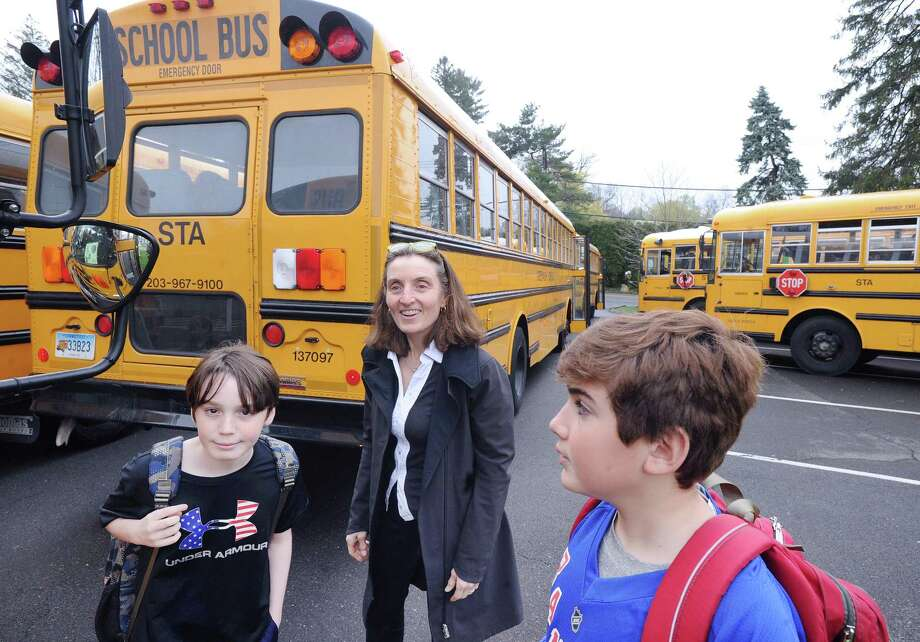 "Greenwich Country Day School Sustainability Director Laura di Bonaventura, center, helps students participating in ""Tiger Rides"" find their school buses at Greenwich Country Day School in Greenwich, Conn., Friday, April 21, 2017.  Tiger Rides is a Greenwich Country Day School program designed to encourage bus riding and carpooling for a better environment. Photo: Bob Luckey Jr. / Hearst Connecticut Media / Greenwich Time"