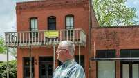 Tom Joines, who grew up in Glen Flora, remembers when the little town was livelier. He is standing in front of the two-story brick building that was Scheller's Place for many years.
