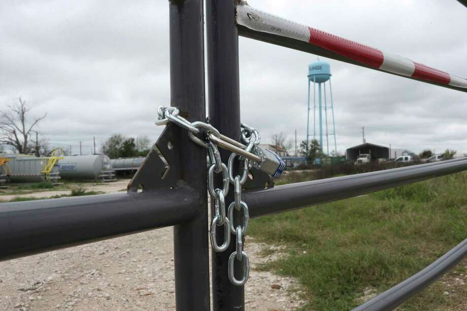 A chain and lock secures the Tank 1 Services lot in Runge, Texas, Thursday, March 10, 2016. It is one of several companies that have filed for bankruptcy in the Eagle Ford Shale counties. Photo: JERRY LARA, Staff / © 2016 San Antonio Express-News