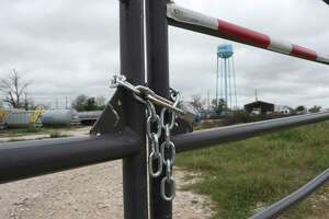 A chain and lock secures the Tank 1 Services lot in Runge, Texas, Thursday, March 10, 2016. It is one of several companies that have filed for bankruptcy in the Eagle Ford Shale counties.