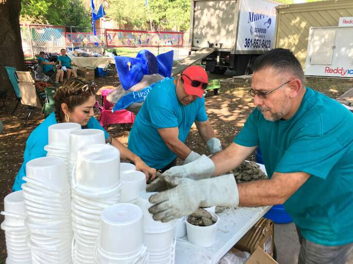 Volunteers prepare the first batch of oysters at the Fiesta Oyster Bake at St. Mary's University.